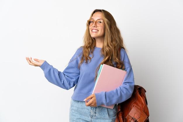 来るように誘うために手を横に伸ばして白い背景で隔離の若い学生女性