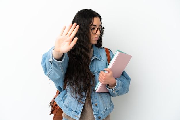 停止ジェスチャーを作る白い背景に孤立し、失望した若い学生女性