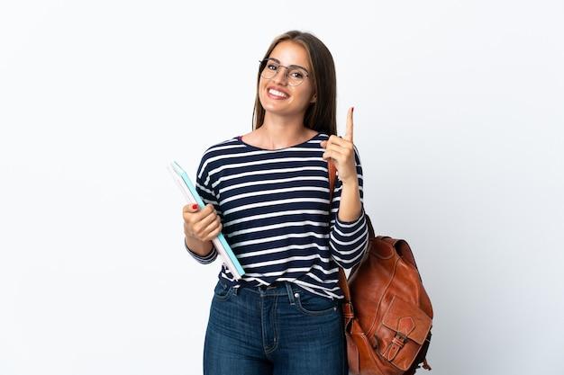Молодая студентка женщина изолирована на белом фоне, показывая и поднимая палец в знак лучших