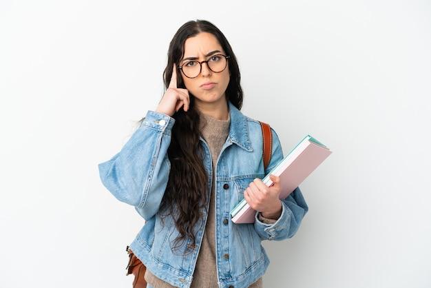 アイデアを考えて白い背景で隔離の若い学生女性