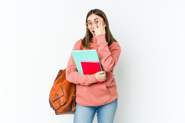 Молодая женщина студента, изолированные на белом bakcground мигает сквозь пальцы, испуганные и нервные.