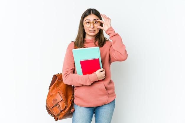 Молодая женщина студента изолированная на белом bakcground держа глаза открытыми, чтобы найти возможность успеха.