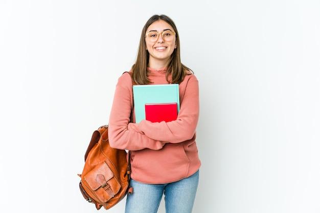 Молодая женщина студента изолированная на белом bakcground смеясь над и имея потеху.