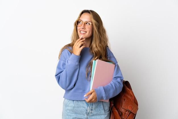 Молодая студентка женщина изолирована на белой стене, глядя вверх, улыбаясь