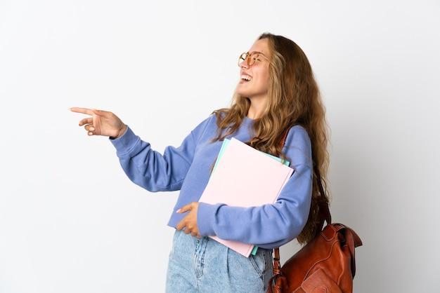 Молодая студентка женщина изолирована на белой стене указывая пальцем в сторону и представляет продукт