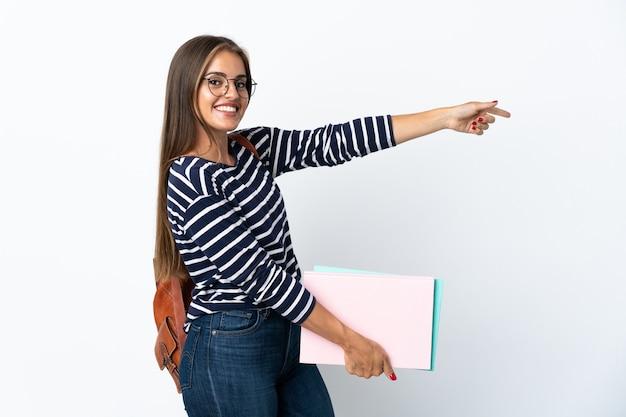 横に指を指し、製品を提示する白い壁に分離された若い学生女性