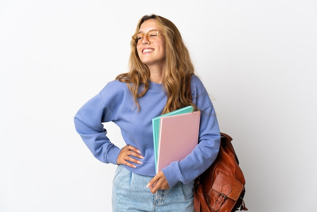 Молодая студентка женщина изолирована на белой стене позирует с руками на бедре и улыбается