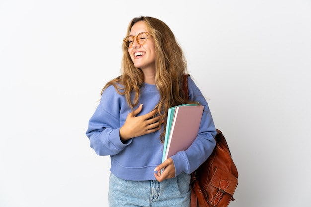 Молодая студентка женщина изолирована на белой стене, много улыбаясь