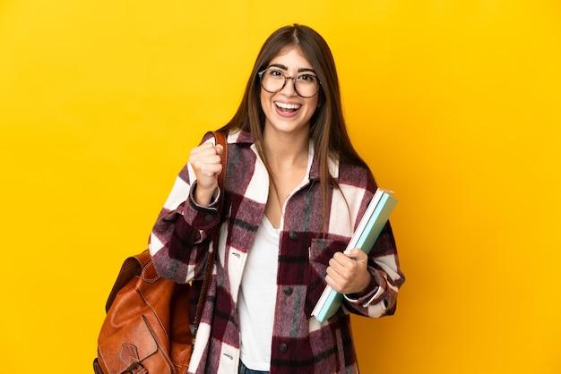 승자 위치에서 승리를 축하하는 노란색 배경에 고립 된 젊은 학생 여자