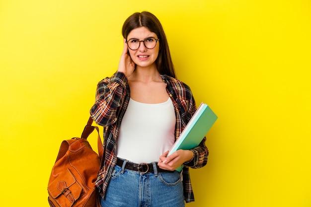 手で耳を覆う黄色の背景に分離された若い学生女性。