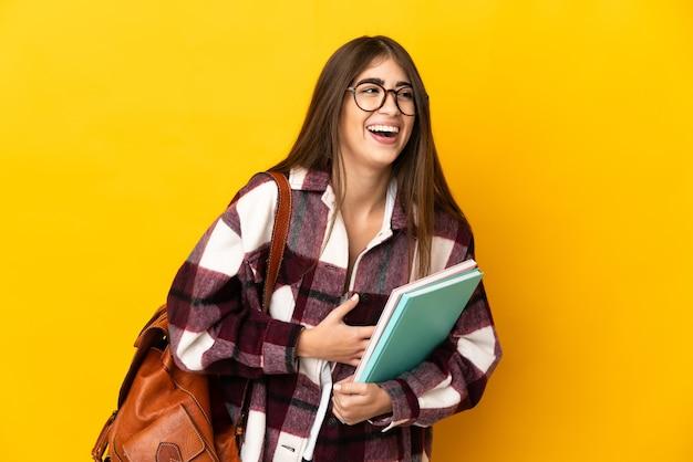たくさん笑って黄色の背景に分離された若い学生女性