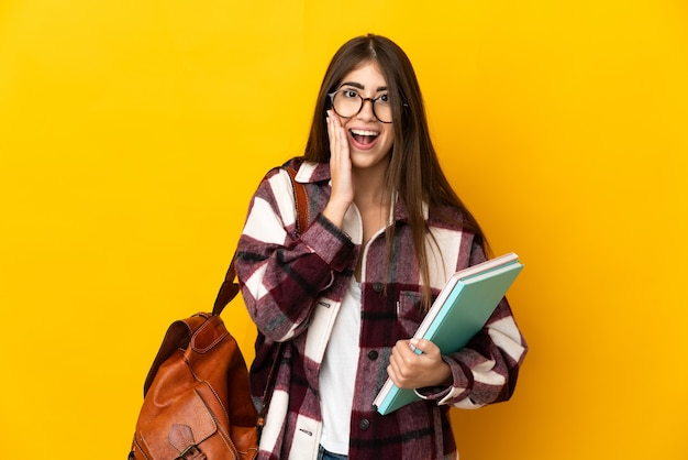 Молодая студентка изолирована на желтом фоне с удивленным и шокированным выражением лица