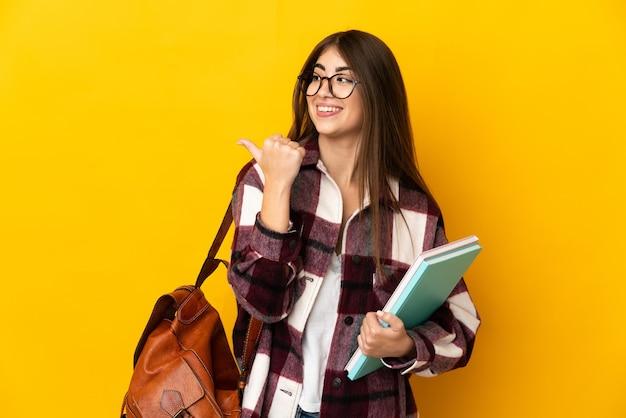製品を提示する側を指している黄色の壁に分離された若い学生女性