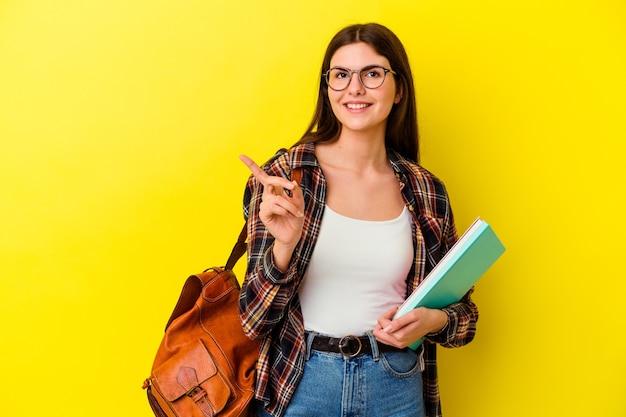 웃 고 옆으로 가리키는 노란색 벽에 고립 된 젊은 학생 여자, 빈 공간에서 뭔가 보여주는