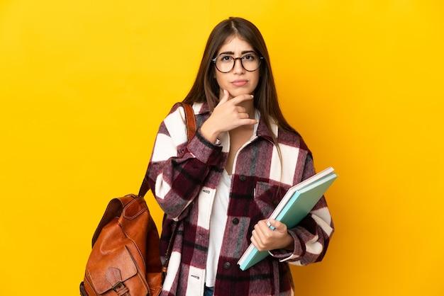 Молодая студентка женщина изолирована на желтой стене мышления