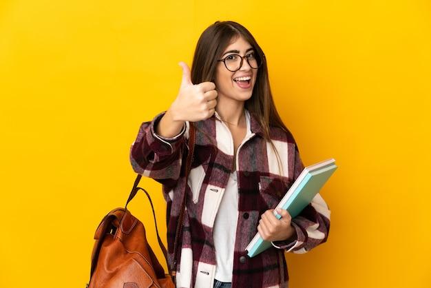 Молодая студентка изолирована на желтой стене с большими пальцами руки вверх, потому что произошло что-то хорошее