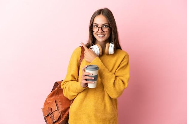 측면을 가리키는 젊은 학생 여자 절연 분홍색 배경