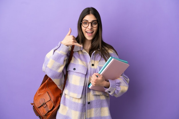 Young student woman isolated on purple background making phone gesture. call me back sign