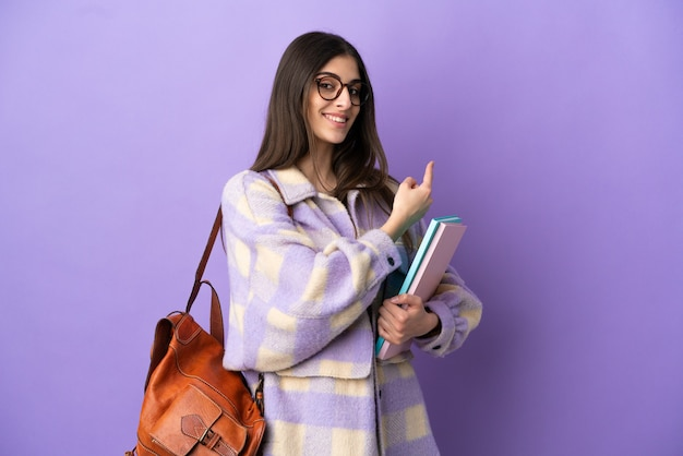 Young student woman isolated on purple background pointing back