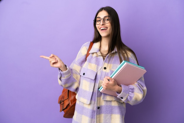 Young student woman isolated on purple background pointing finger to the side
