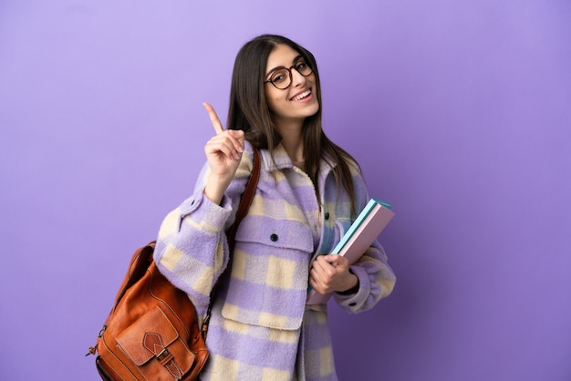 Young student woman isolated on purple background showing and lifting a finger in sign of the best