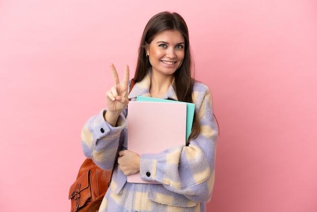 Молодая студентка женщина изолирована, улыбаясь и показывая знак победы