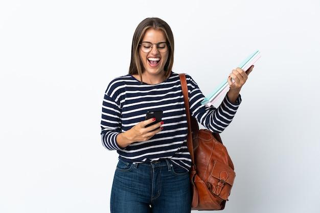 Молодая студентка женщина изолирована с телефоном в позиции победы