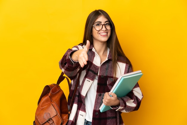 Young student woman isolated on yellow background shaking hands for closing a good deal