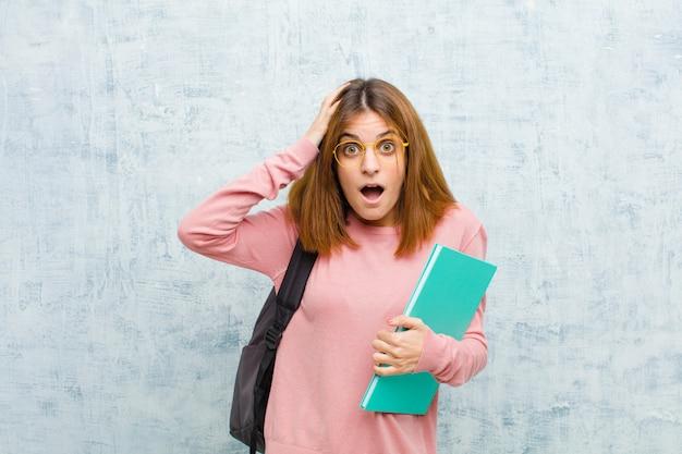 Молодой студент женщина выглядит взволнован и удивлен, с открытым ртом обеими руками на голову, чувствуя себя счастливым фоном победителя
