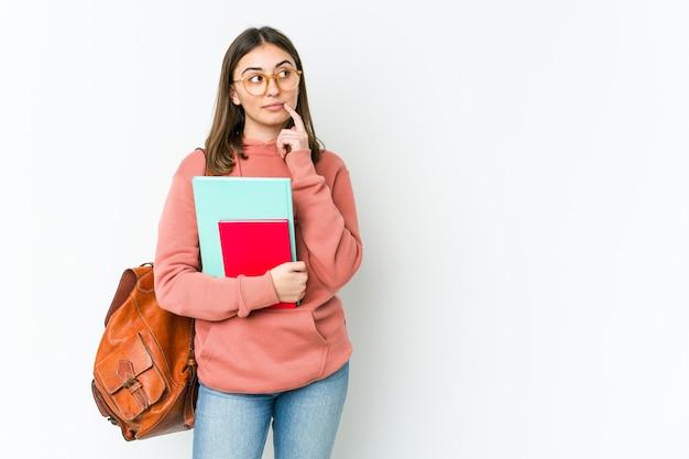 Молодая студентка смотрит в сторону с сомнительным и скептическим выражением лица