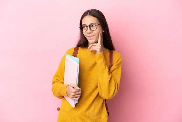 찾는 동안 아이디어를 생각하는 격리 된 배경 위에 젊은 학생 여자