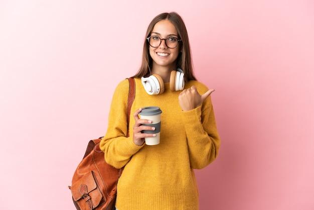 製品を提示する側を指している孤立したピンクの背景上の若い学生女性