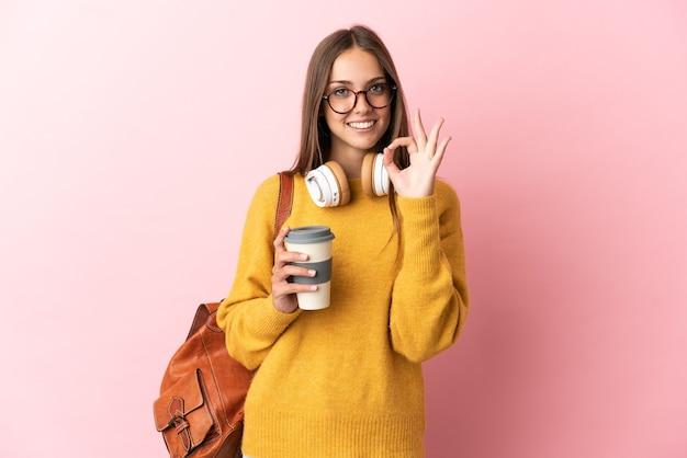 손가락으로 확인 표시를 보여주는 고립 된 분홍색 배경 위에 젊은 학생 여자