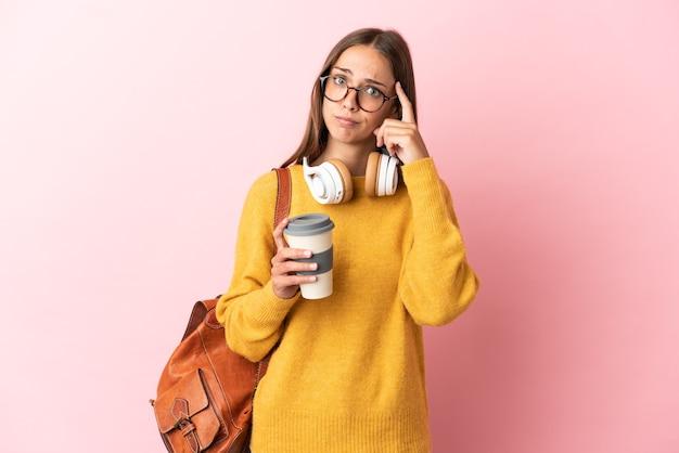 아이디어를 생각하는 고립 된 분홍색 배경 위에 젊은 학생 여자