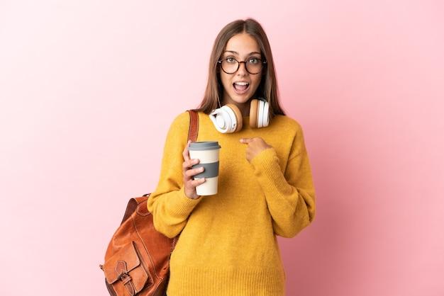 놀라운 표정으로 고립 된 분홍색 배경 위에 젊은 학생 여자