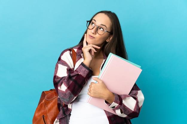 Молодая студентка женщина над изолированной стеной думает об идее, глядя вверх