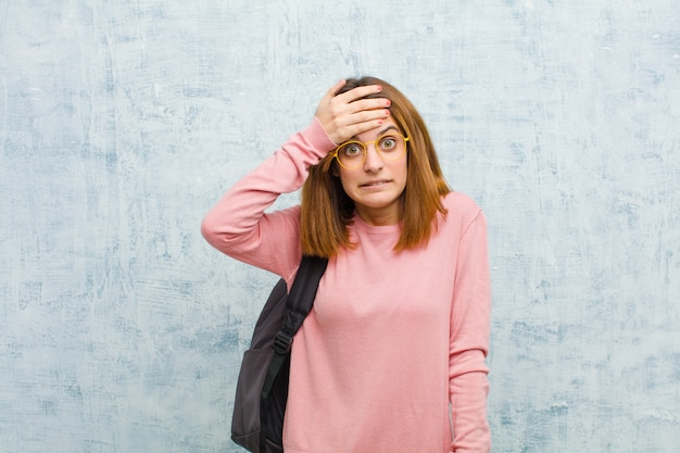 Young student woman panicking over a forgotten deadline, feeling stressed, having to cover up a mess or mistake