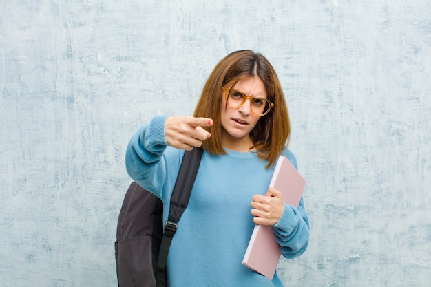 Young student woman pointing at camera with an angry aggressive expression looking like a furious, crazy boss against grunge wall wall