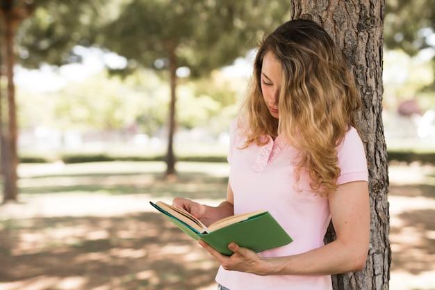 Молодая книга чтения женщины студента в парке
