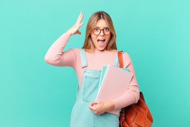 Молодая студентка женщина кричит с поднятыми руками в воздухе