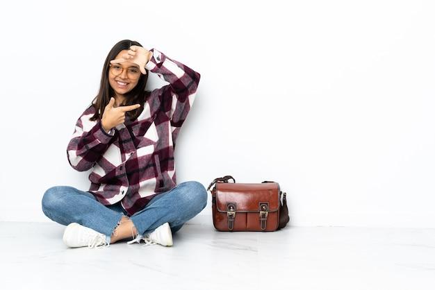 Молодая студентка женщина сидит на полу, фокусируя лицо