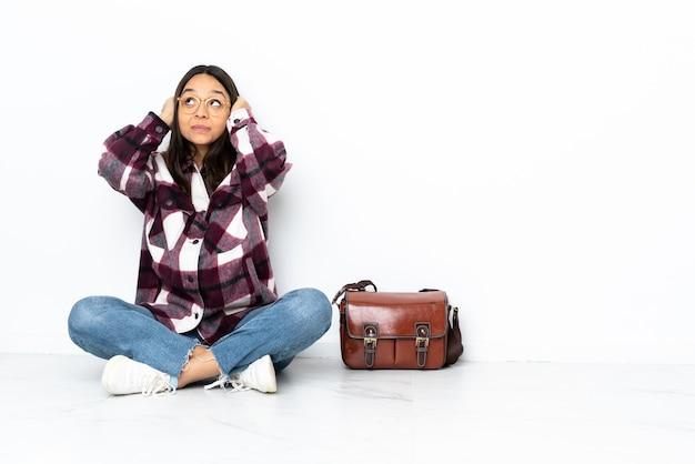 欲求不満で耳を覆っている床に座っている若い学生女性