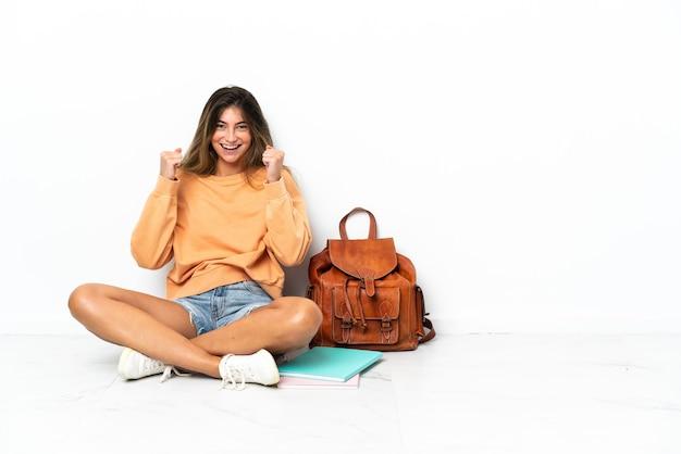 승자 위치에서 승리를 축하하는 흰색 배경에 고립 된 노트북과 함께 바닥에 앉아 젊은 학생 여자