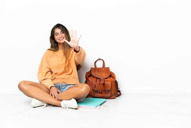 손가락으로 5 세 흰색 배경에 고립 된 노트북과 함께 바닥에 앉아 젊은 학생 여자
