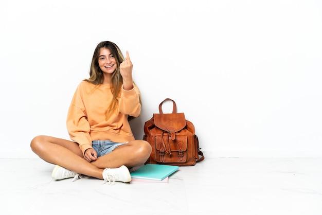 오는 제스처를 하 고 흰색 배경에 고립 된 노트북과 함께 바닥에 앉아 젊은 학생 여자