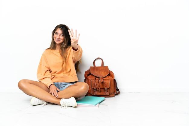 노트북 바닥에 앉아 젊은 학생 여자는 행복하고 손가락으로 4 세 흰색 배경에 고립
