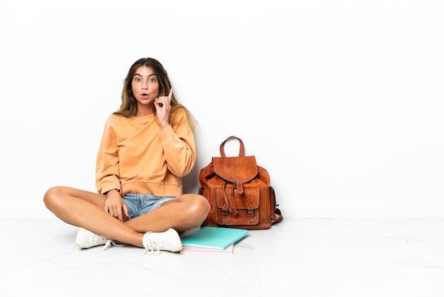 손가락을 들어 올리는 동안 솔루션을 실현하려는 흰색 배경에 고립 된 노트북과 함께 바닥에 앉아 젊은 학생 여자