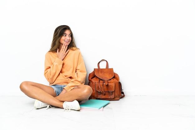 웃는 동안 찾고 흰색 배경에 고립 된 노트북과 함께 바닥에 앉아 젊은 학생 여자