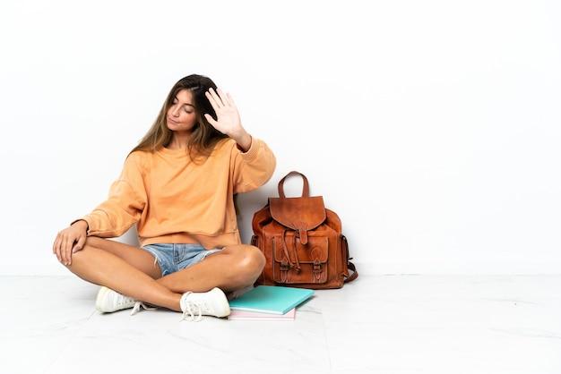 노트북 바닥에 앉아 젊은 학생 여자 중지 제스처를 만드는 흰색 배경에 고립 실망