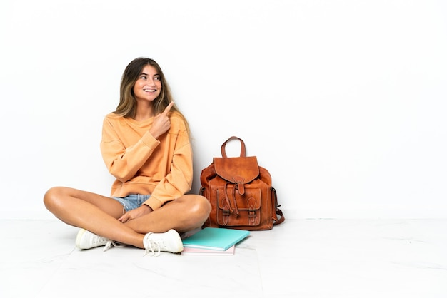제품을 제시하는 측면을 가리키는 흰색 배경에 고립 된 노트북과 함께 바닥에 앉아 젊은 학생 여자